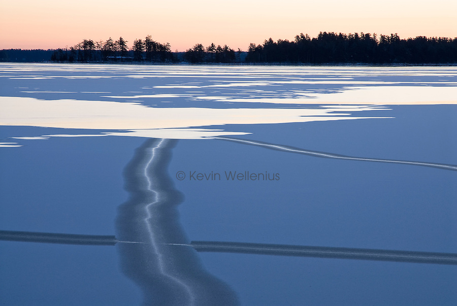 Sunrise reveals cracks and the last open water as the ice forms over Great Pond in the Belgrade Lakes region of central Maine.