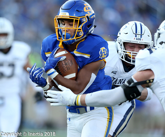 BROOKINGS, SD, SEPTEMBER 8: Cade Johnson #15 from South Dakota State University slips between a pair of defenders from Montana State for a touchdown in the first half of their game Saturday night at Dana J Dykhouse Stadium in Brookings, SD. (Dave Eggen/Inertia)
