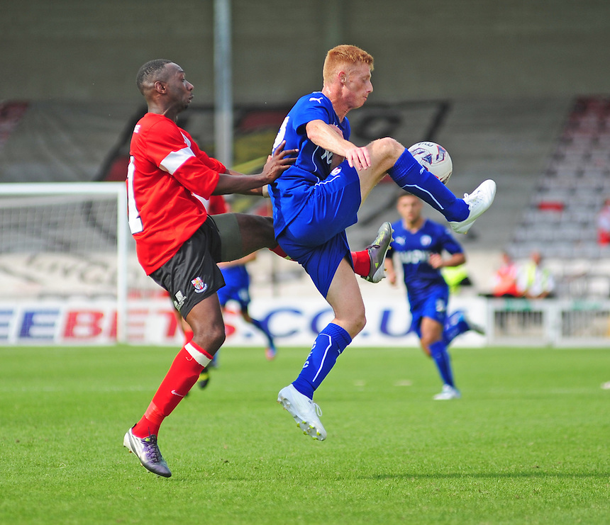 Chesterfield's Eion Doyle shields the ball from Lincoln City's Nat Brown<br /> <br /> Photographer Chris Vaughan/CameraSport<br /> <br /> Football - Friendly - Lincoln City v Chesterfield - Saturday 19th July 2014 - Sincil Bank Stadium - Lincoln<br /> <br /> &copy; CameraSport - 43 Linden Ave. Countesthorpe. Leicester. England. LE8 5PG - Tel: +44 (0) 116 277 4147 - admin@camerasport.com - www.camerasport.com