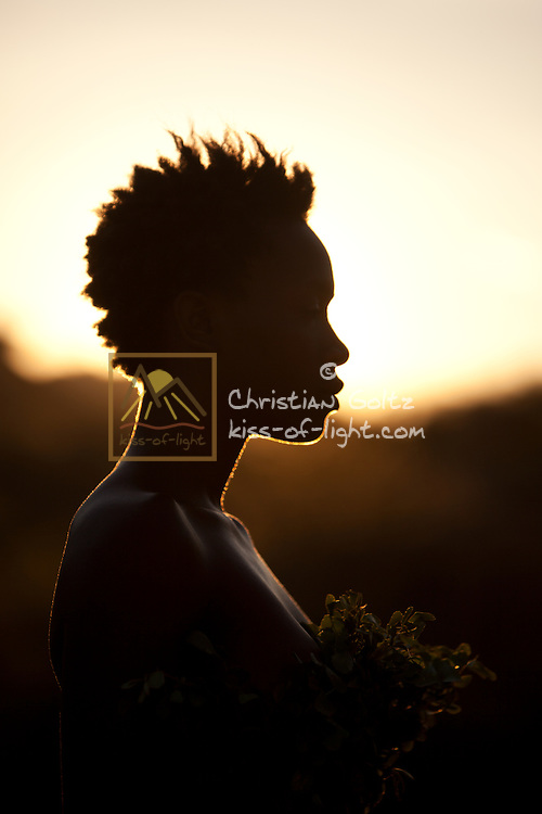 Young black girl in mountain setting with afro hairstyle wearing leaves backlit by the setting sun.