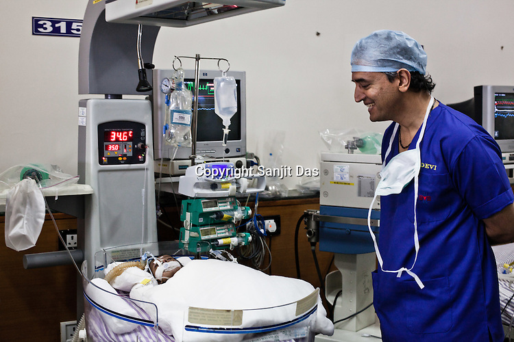 Heart Surgeon, Dr. Devi Prasad Shetty checks on 22 days old Praseetha as she lies on the bed at the Intensive Therapy Unit of the Pediatric Section of the Narayana Hrudayalaya in Bangalore, Karnataka, India. Photo: Sanjit Das/Panos