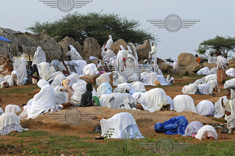 Worshippers in white robes pray outside St Mary's church during a baptism in the village of Fithi ('justice'). .