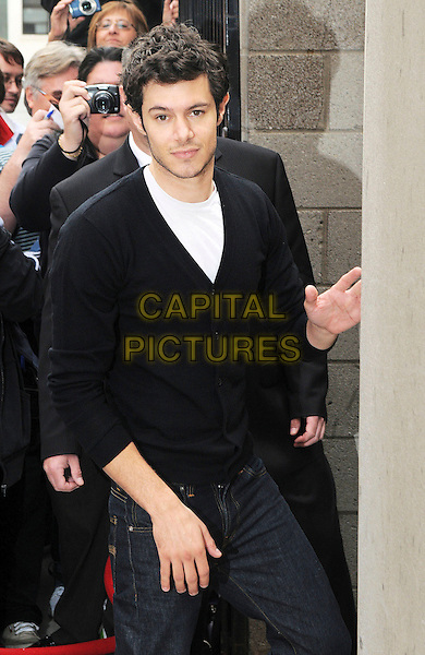 "ADAM BRODY .""Jennifer's Body"" outside arrivals for the Premiere held at Ryerson Theatre during the 35th Annual Toronto International Film Festival, Toronto, Ontario, Canada,.12th September 2009..half length black cardigan hand waving white t-shirt jeans denim .CAP/ADM/BPC.©Brent Perniac/Admedia/Capital Pictures"
