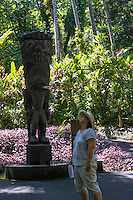 "A woman looks up near a carved wooden tiki of the Hawaiian god ""KU"" at Hawaii Tropical Botanical Garden, Papa'ikou, Big Island of Hawaiʻi."