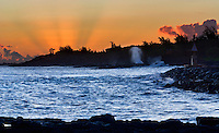 Spouting Horn comes to life as the suns rays shine from behind the hills at Kukuiula Harbor, Kauai.