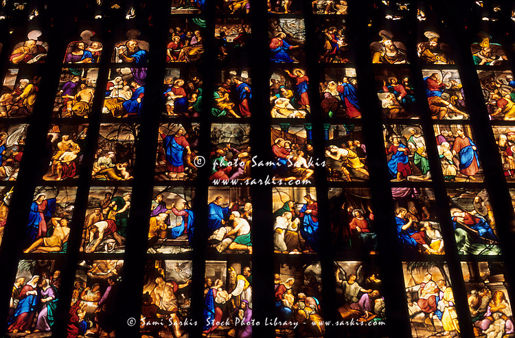 Brightly colored stained glass window depicting a religious story inside the Milan Cathedral, Milan, Italy.