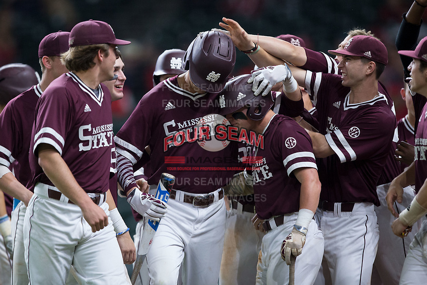 Tanner Poole (center) is congratulated by his Mississippi State Bulldogs teammates after his solo home run in the top of the ninth inning gave them the lead over the Louisiana-Lafayette Ragin' Cajuns in game three of the 2018 Shriners Hospitals for Children College Classic at Minute Maid Park on March 2, 2018 in Houston, Texas.  The Bulldogs defeated the Ragin' Cajuns 3-1.   (Brian Westerholt/Four Seam Images)