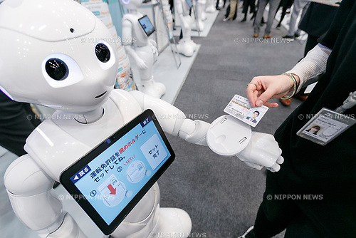 An exhibitor gives a demonstration of an ID scanning application though humanoid robot Pepper during SoftBank Robot World 2017 on November 21, 2017, Tokyo, Japan. SoftBank Robotics organized SoftBank Robot World 2017 to introduce AI (Artificial Intelligence) and IoT (the Internet of Things) companies developing the latest technology for robots, including applications its humanoid robot Pepper in various business fields. The robot expo runs until November 22. (Photo by Rodrigo Reyes Marin/AFLO)