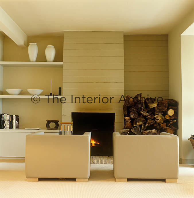 In this living room two armchairs are placed in front of a fireplace next to which is stored a large stack of logs