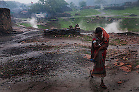 A mother carries her baby to a shelter from the rain. Behind her fumes can be seen coming out from the ground due to burning coal seams beneath it. A huge coal mine fire is engulfing the city of Jharia from all its sides. All scientific efforts have gone in vain to stop this raging fire. This fire is affecting lives of people living in and around Jharia. Jharkhand, India. Arindam Mukherjee.