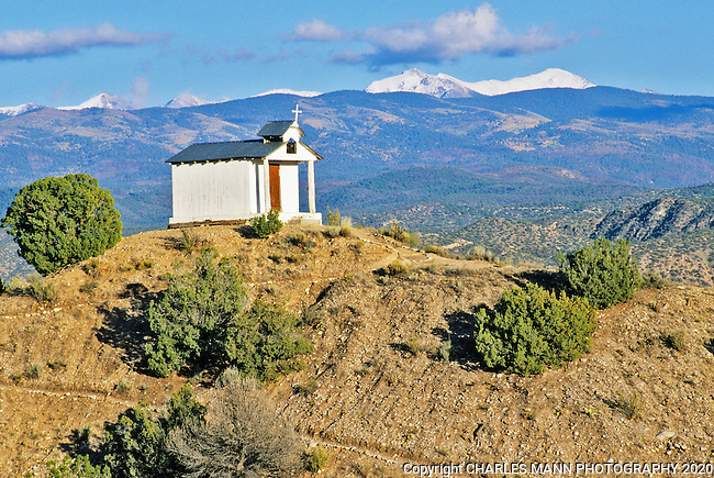 Framed by the distant snow covered Sangre de Cristo Mountains, the tiny Santa Rita Chapel stands on a hill top between the town of Espanola and the village of Chimayo in northern New Mexico.