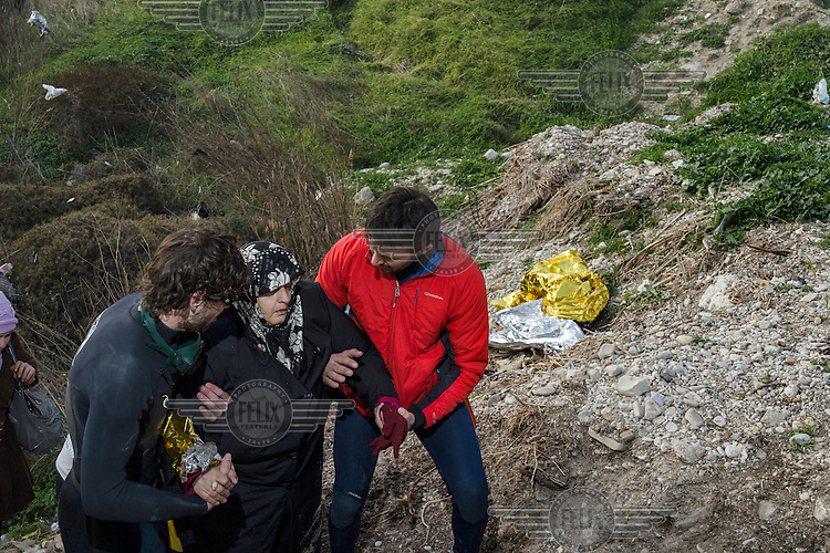 A man from the UNHCR, Spanish lifeguards, a Danish volunteer and a local man help an elderly refugee up from the beach where the boat she was on landed.