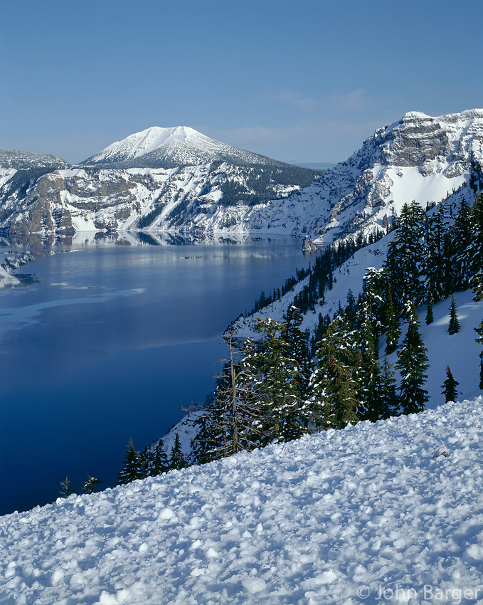ORCL_014 - USA, Oregon, Crater Lake National Park, Evening light warms snowy rim of Crater Lake in late afternoon and distant Mount Scott.