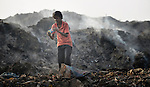 A boy inspects a find as he scavenges in the smoldering municipal garbage dump in Chennai, India. He and other boys who work in the dump spend their nights safely in a shelter sponsored by the Madras Christian Council of Social Service.