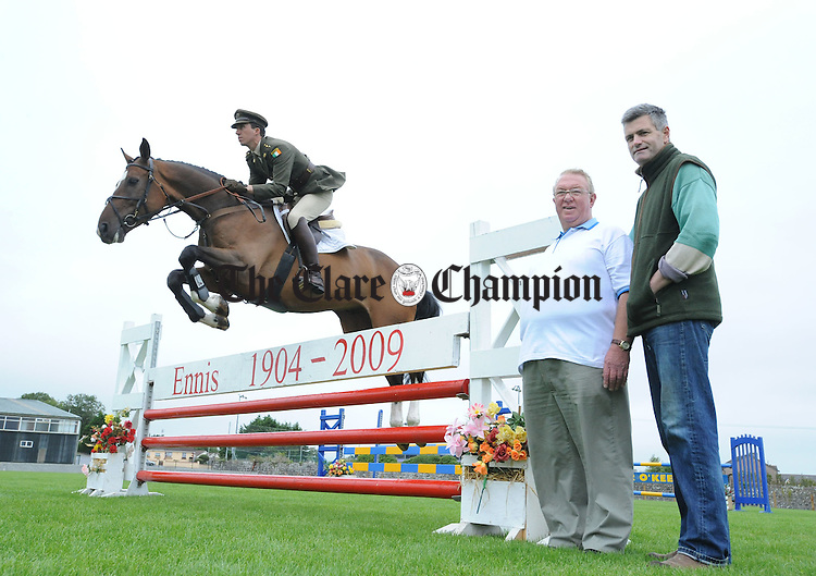 Jimmy Quinn and Dermot Costello from the Clare County Agricultural Show watch Captain Sean Carey of the Army Equitation School warm up at Ennis Showgrounds for this year's show. Photograph by Declan Monaghan