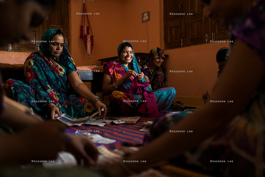 Mamta Jat (centre), 35, learns how to sew a garment in a stitching course taught by Kavita Yadav who is hired using the Fairtrade Premiums to teach in Maheshwar, Khargone, Madhya Pradesh, India on 13 November 2014. Mamta's husband is a Fairtrade cotton farmer, but the stitching course, is free for all interested women from the village, both Fairtrade or not. Photo by Suzanne Lee for Fairtrade