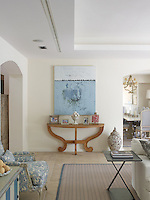 A large canvas painted in tones of blue and white hangs above a curved console table displaying family framed photographs