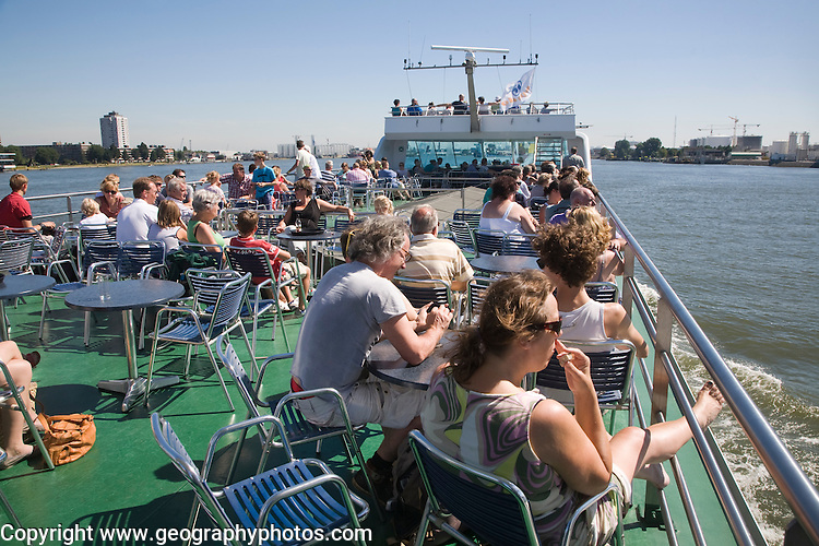 People sitting on the deck of a tour Spido boat in summer, Port of Rotterdam, Netherlands