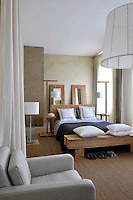 Linen in muted shades softens the effect of the plain and rustic wooden furniture in the bedroom
