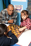 Afterschool chess program for elementary students graduates of Headstart program male teacher working with two girls