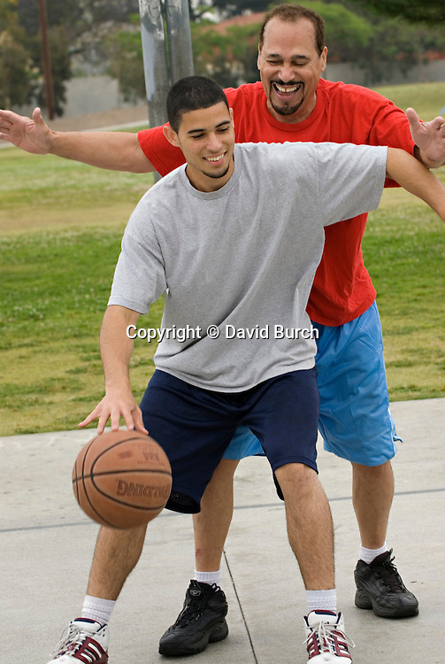 Hispanic man and his son playing basketball