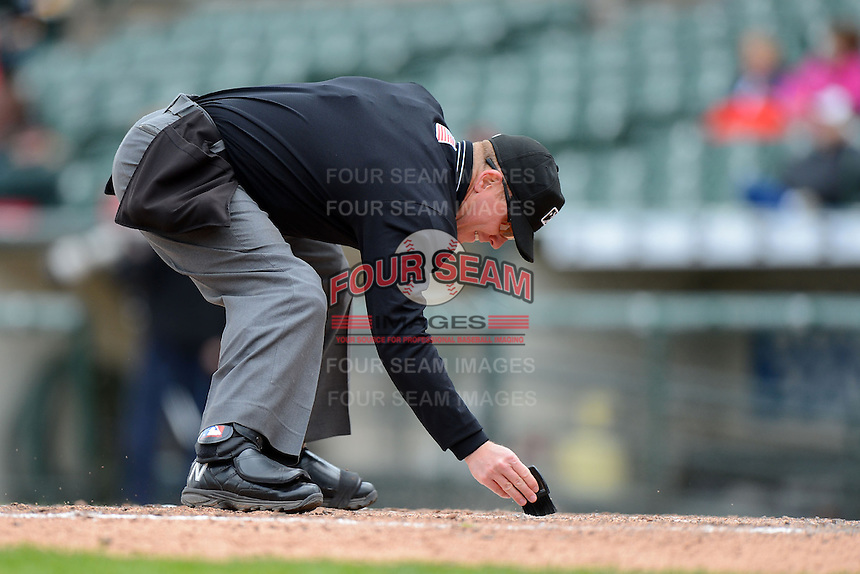 Umpire Toby Basner cleans off the plate during a game between the Columbus Clippers and Rochester Red Wings on May 12, 2013 at Frontier Field in Rochester, New York.  Rochester defeated Columbus 5-4.  (Mike Janes/Four Seam Images)