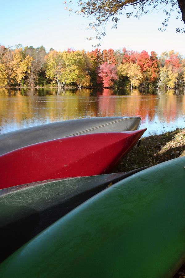 Canoes on riverbank with foliage reflection on river