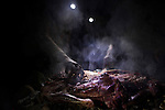 Domestic Goat (Capra hircus) being grilled at night, Dhofar Mountains, Oman