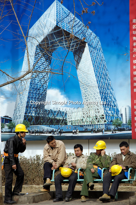 Chinese workers have a rest in front of a billboard of new headquarters for China Central Television (CCTV) outside the construction site in Beijing, China. .