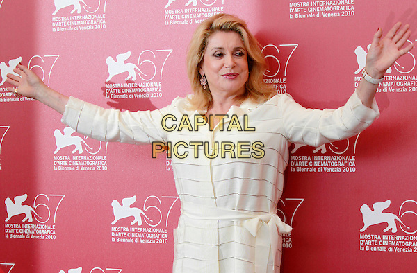 "CATHERINE DENEUVE.""Potiche"" photocall, 67th Venice International Film Festival, Venice, Italy..September 4, 2010.half length white stripe dress hands arms outstretched .CAP/PE.©Peter Eden/Capital Pictures."
