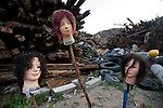 The heads of three manikin used for training at hair salons are set upon wooden sticks at a waste collection site where debris from the March 11 tsunami is collected and sorted in Yamada Town, Iwate Prefecture, Japan on  10 June 2011.  Authorities are unable to dispose of much of the debris created by the March disasters due to fears of radiation contamination, leading to giant mounds of waste that are becoming increasingly more toxic. The disaster is estimated to have left behind some 25 million tons of waste. Photographer: Robert Gilhooly