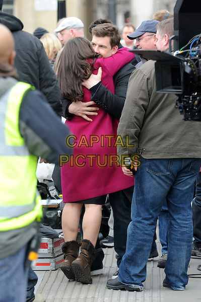 AMERICA FERRERA & ERIC MABIUS.filming 'Ugly Betty' on location in Trafalgar Square, London, .England, UK, 5th April 2010.filmset filmset full length red pink coat back rear behind hug hugging brown uggs ugg boots .CAP/IA.©Ian Allis/Capital Pictures.