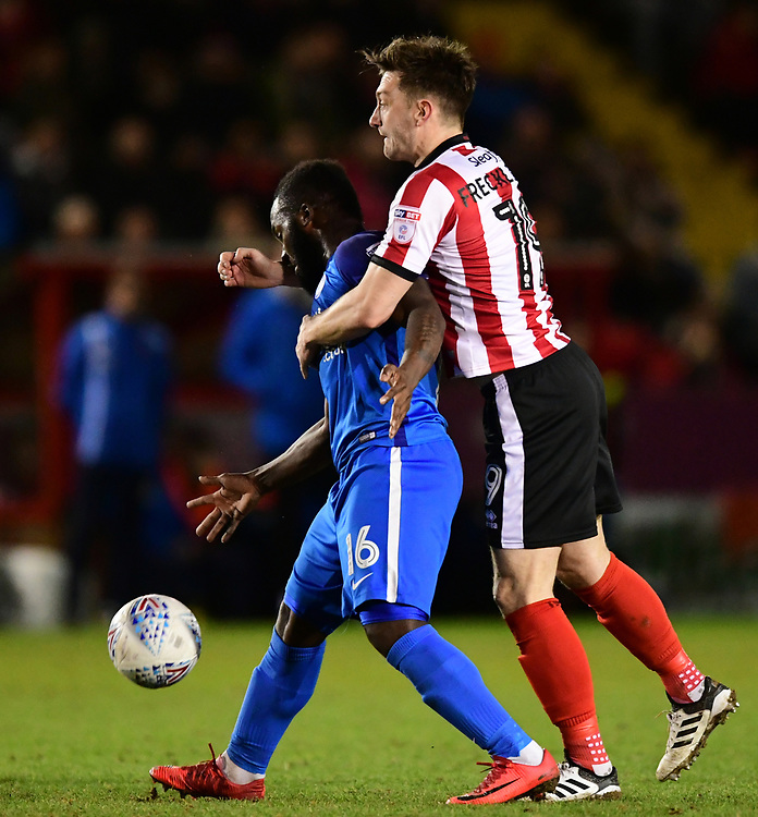Lincoln City's Lee Frecklington vies for possession with Peterborough United's Junior Morias<br /> <br /> Photographer Chris Vaughan/CameraSport<br /> <br /> The EFL Checkatrade Trophy Fourth Round - Lincoln City v Peterborough United - Tuesday 23rd January 2018 - Sincil Bank - Lincoln<br />  <br /> World Copyright &copy; 2018 CameraSport. All rights reserved. 43 Linden Ave. Countesthorpe. Leicester. England. LE8 5PG - Tel: +44 (0) 116 277 4147 - admin@camerasport.com - www.camerasport.com