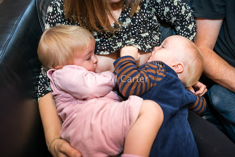 A young woman breastfeeds her twins together at the same time while sitting on a sofa in a public library.<br /> <br /> 24/11/12<br /> Hampshire, England, UK