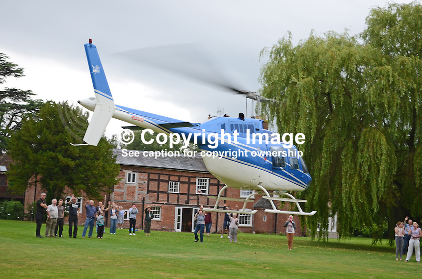 Private helicopter, G-RUCK, takes off from the grounds of Elm Lodge, Fishmore, Ludlow, Shropshire, UK, to bring four secondary school pupils to their school's formal end of term dance, also referred to as a prom. 201407043215<br />