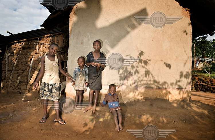 Three year old Daniel Namoso Robert and his sister nine year old Robinah Gimoao (centre) stand with two friends outside their home.