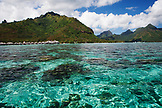 FRENCH POLYNESIA, Moorea. Reefs along the coast of Moorea Island. Partial view of the Hilton Moorea Lagoon Resort & Spa in the background.