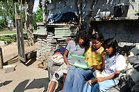 URUGUAY Montevideo, OLPC One Laptop per Child project, the 100 Dollar laptop initiative of Nicholas Negroponte, is implemented in Uruguay for children at all schools under Plan Ceibal, laptops also have access to the internet, girl Mimosa Almeida with mother and brother in suburb La Bolyada / URUGUAY Montevideo, fuer alle Kinder an  staatlichen Schulen Uruguays ist das OLPC one laptop per child Programm als Bildungsinitiative Plan Ceibal umgesetzt , jedes Kind bekommt einen 100 Dollar Laptop XO-1 und Zugang zum W-lan Netz der Schule
