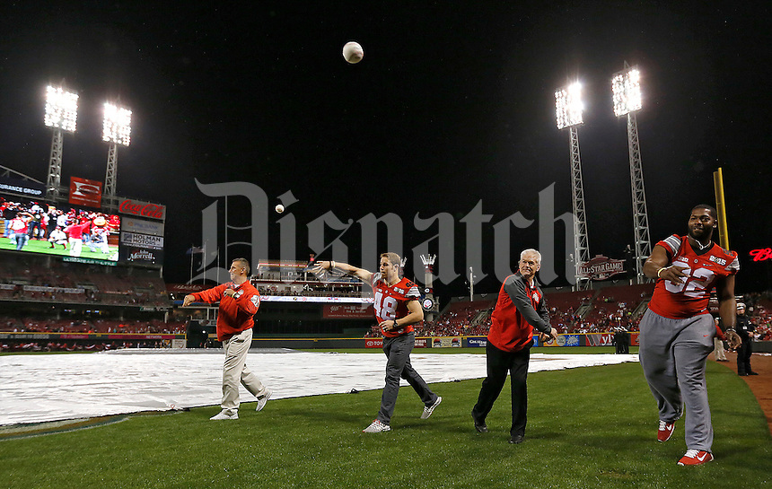 Ohio State head coach Urban Meyer, linebacker Joe Burger, asst. coach Kerry Coombs and defensive lineman Adolphus Washington throw out ceremonial first pitches prior to the rain delayed Cincinnati Reds game against Pittsburgh at Great American Ball Park on Wednesday, April 8, 2015. (Columbus Dispatch photo by Jonathan Quilter)