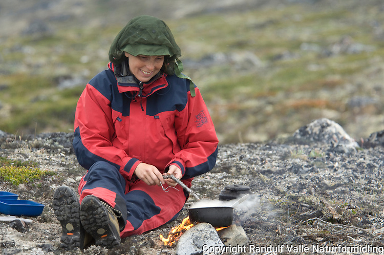 Jente lager mat på lite bål ---- Girl cooking on small camp fire