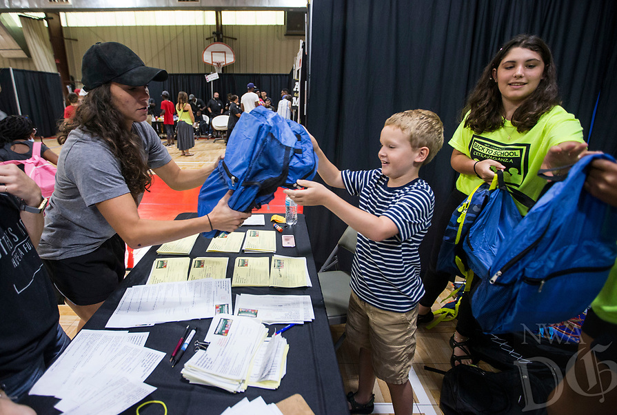 NWA Democrat-Gazette/BEN GOFF @NWABENGOFF<br /> Rebecca Frey (from left), a staff member at Potter's House, picks up backpacks filled with school supplies for children in their programs from Carter Johnson, 8, and Angelica Sikes, both from Fayetteville and volunteering with a group from Camp War Eagle, Saturday, Aug. 10, 2019, during the Northwest Arkansas Community Back to School Extravaganza at the Yvonne Richardson Community Center in Fayetteville. Four area churches; St. James Missionary Baptist Church, Good Shepherd Lutheran Church, Agape Ministries and New Heights, partnered to put on the event. Community partners provided free vision and dental screenings, haircuts, blood pressure checks for parents and backpacks full of school supplies. The Ronnie Brewer Foundation and Northwest Arkansas Collision Center donated the supplies to fill the backpacks.