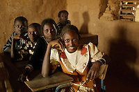 Muna, wearing white flowered dress, sits in a classroom in the village of Intedeyne. The challenge to educate children in Mali still exists and particularly for girls. Female literacy rates never reach even 50 percent of male literacy rates. Mali has the highest percentage of people living below the poverty line in any country in the world. Ninety percent of Malians survive on less than two dollars a day. /Felix Features