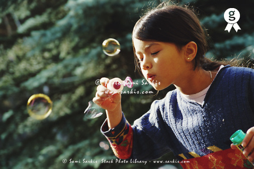 Girl (7-9) blowing bubble-wand, outdoors (Licence this image exclusively with Getty: http://www.gettyimages.com/detail/200387443-001 )