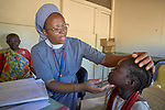 Sister Catherine Tukay, a Precious Blood sister and nurse from Tanzania, examines a young patient in the Catholic clinic in Kauda, a village in the Nuba Mountains of Sudan. The area is controlled by the Sudan People's Liberation Movement-North, and frequently attacked by the military of Sudan. The Catholic Church has dug wells and sponsors schools and health care facilities throughout the war-torn region.