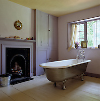 A free-standing roll-top bath painted in silver stands in the middle of a lilac-coloured bathroom
