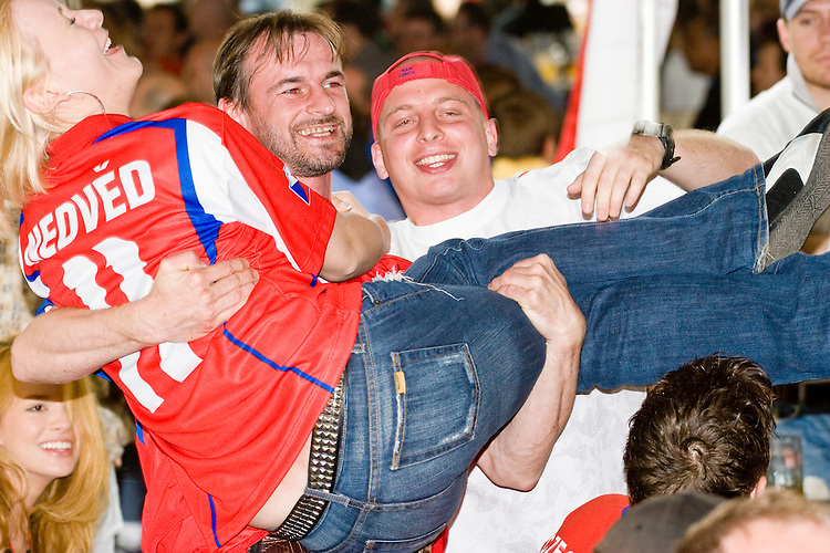 Vladimir Turek lifts Monika Uherik while Tomas Hudecek cheers on after a Czech Republic victory against the United States at the Bohemian Hall and Beer Garden in New York City on June 12, 2006.<br /> <br /> The World Cup, held every four years in different locales, is the world's pre-eminent sports tournament in the world's most popular sport, soccer (or football, as most of the world calls it).  Qualification for the World Cup is open to any country with a national team accredited by FIFA, world soccer's governing body. The first World Cup, organized by FIFA in response to the popularity of the first Olympic Games' soccer tournaments, was held in 1930 in Uruguay and was participated in by 13 nations.    <br /> <br /> As of 2010 there are 208 such teams.  The final field of the World Cup is narrowed down to 32 national teams in the three years preceding the tournament, with each region of the world allotted a specific number of spots.  <br /> <br /> The World Cup is the most widely regularly watched event in the world, with soccer teams being a source of national pride.  In most nations, the whole country is at a standstill when their team is playing in the tournament, everyone's eyes glued to their televisions or their ears to the radio, to see if their team will prevail.  While the United States in general is a conspicuous exception to the grip of World Cup fever there is one city that is a rather large exception to that rule.  In New York City, the most diverse city in a nation of immigrants, the melting pot that is America is on full display as fans of all nations gather in all possible venues to watch their teams and celebrate where they have come from.
