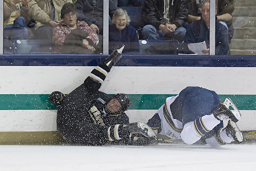 Notre Dame defenseman Stephen Johns (#28) checks Western Michigan right wing Dane Walters (#23) into the boards in first period action of NCAA hockey game between Notre Dame and Western Michigan.  The Western Michigan Broncos defeated the Notre Dame Fighting Irish 3-2 in game at the Compton Family Ice Arena in South Bend, Indiana.