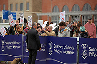 Pictured: A security guard speaks to anti-Hillary Clinton protesters at Swansea University Bay Campus. Saturday 14 October 2017<br /> Re: Hillary Clinton, the former US secretary of state and 2016 American presidential candidate will be presented with an honorary doctorate during a ceremony at Swansea University's Bay Campus in Wales, UK, to recognise her commitment to promoting the rights of families and children around the world.<br /> Mrs Clinton's great grandparents were from south Wales.