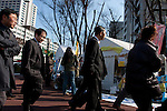 Government workers in suits walk past an anti-nuclear power demo and occupy Tokyo protest outside the Ministry of the Economy, Trade and Industry (METI) in Tokyo, Japan. Friday 27th January 2012. The protest has been running from September 2011 and was scheduled for forcible eviction by police at 5pm on January 27th as the camp had been declared a fire risk by Minister Yukio Edano, with around 500 supporters and protesters turning up to resist the eviction however the camp was still in place the night of the 27th.
