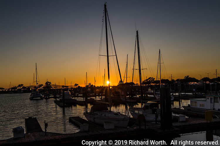 The setting sun partially hidden by the mast of one of the remaining boats moored at the San Leandro Marina on the eastern shores of San Francisco Bay.